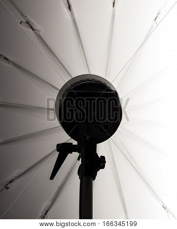 Studio flash silhuette with umbrella behind it.