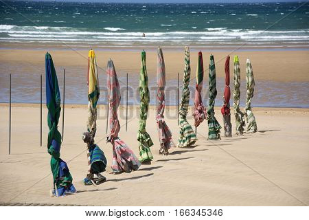 Photo of several sunshades with beach, sea and sunlight