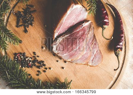 smoked ham with pepper and cloves on a wooden board decorated with fir