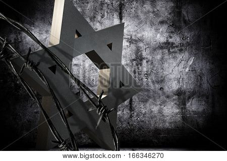 Conceptual background in memoriam of the Shoah Day representing a granite star of David barbed wire.