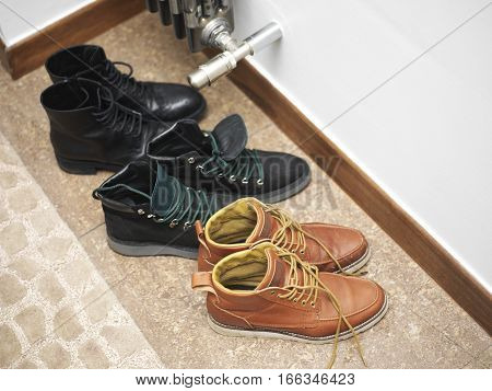 Bunch of a demi-season footwear next to a central heating radiator drying on the floor