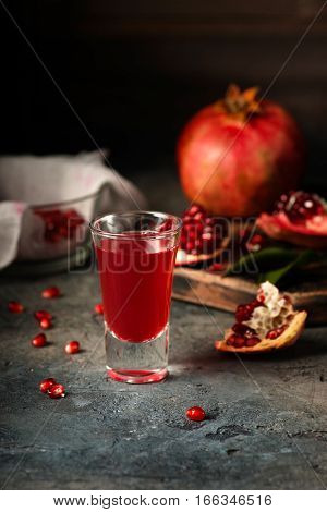 Glass of pomegranate juice. Pomegranate fruits with grains and leaves on the table. Make pomegranate juice. Top view. Dark moody.