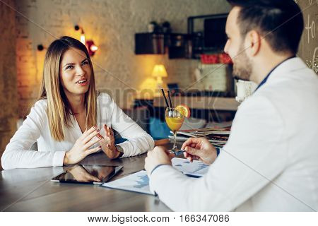 Young business woman and man at a meeting in a cafe