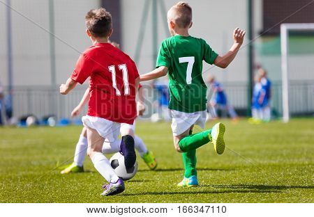 Little boys playing football soccer game on sports field