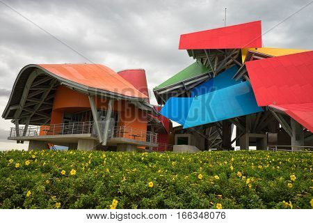 June 13 2016 Panama City Panama: the colourful building of Biomuseum with blooming flowers in the front