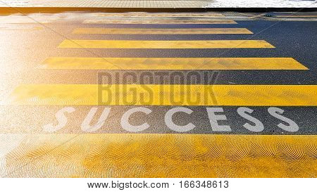 The word success on the road at the crosswalk background business for concept.