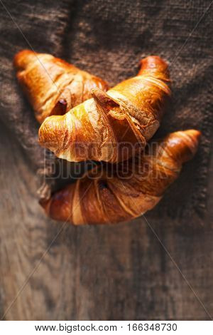 Golden fresh croissants on old wooden background close up with copyspace rustic concept