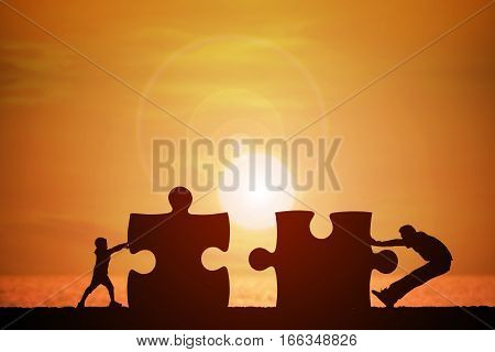 Silhouette of a man and children were pushed into jigsaw splice with beautiful sunset background concept for business success and teamwork.