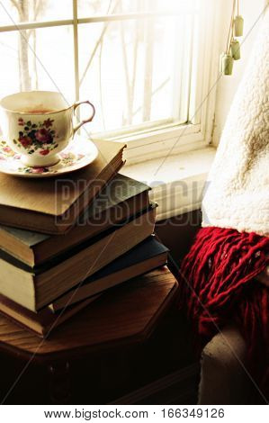 Antique floral teacup on book pile, by white sunlit windowsill next to warm cozy chair.