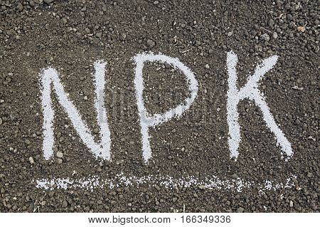 NPK letters made of composite mineral fertilizers on the black soil background. N - nitrogen P - phosphorus K - potassium (kalium)