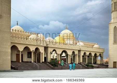 Muslim mosque with two minarets cloudy weather women going to it horizontal