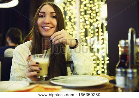 Beautiful young woman drinking coffee at cafe