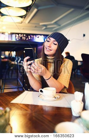 Portrait of beautiful girl using her mobile phone in cafe