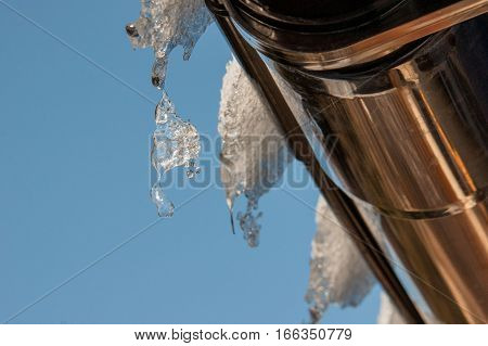 icicles dripping from the roof of the house on a background of blue sky