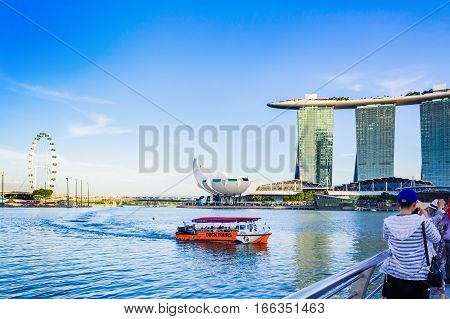 Singapore - January 07 2017: Tourists on Ducktour Boat in Marina Bay and Marina Bay Sands Hotel with fine weather in evening.