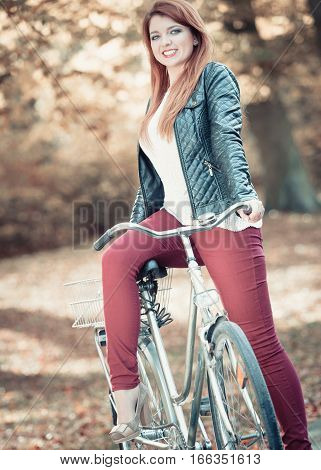 Nature people concept. Ginger hair lady on the bike. Posing with bicycle in autumnal scenery.