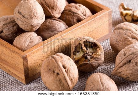 Macro View Of Walnuts Close Up In A Wooden Box On Gray Burlap