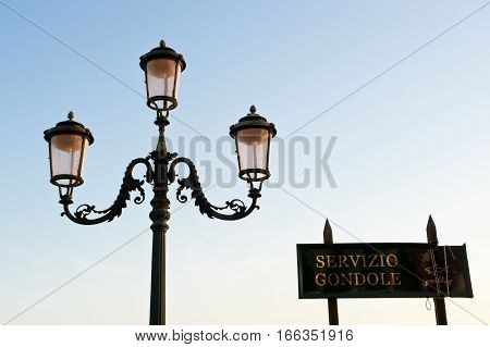 A venetian lamppost and an advertising sign for gondolas service in Venice. Italy