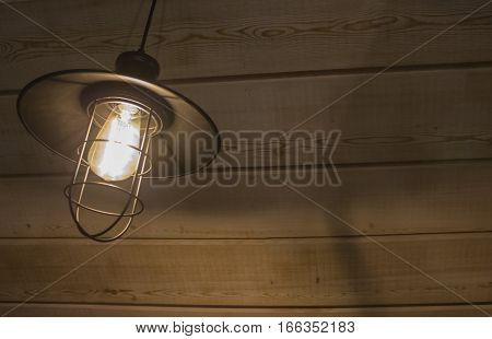 Old fashioned vintage lantern lamp burning with a soft glow light in an antique rustic country barn with aged wood wall and weathered wooden floor.