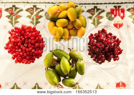 Fresh fruits perfect source of vitamins. Pomegranate, feijoa, red berry and kumquat healthy food for all seasons of the year.