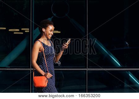 Smiling Young African Woman Walking With Phone And Earphones