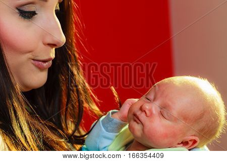 Family motherhood concept. Mother holding her little newborn baby. Red background.