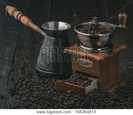 Coffee grinder and jezva with coffee beans on dark wooden background