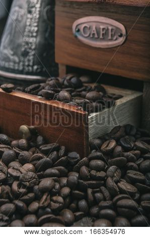 Close up coffee beans with vintage handle grinder