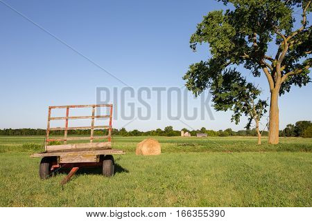 Hay wagon and hay bale in a farm field under a large tree. Copy space in sky if needed and a farm in the distant background.