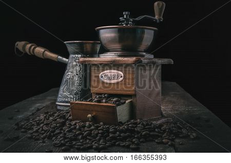 Vintage coffee grinder with beans and jezve on dark background
