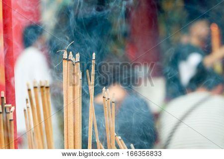 Incense Joss Stick Burning Slowly With Fragrant Smell Smoke. People Praying On Chinese Buddhist Temp