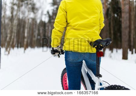 Woman on bicycle in woods at winter day