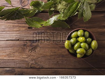 Green olives in a ceramic bowl on a wooden background. Background of olives. Background with green olives. Olives. Copyspace. Green olives and branch of bay leaf. Bay leaf. Copyspace