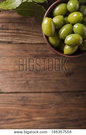 Green olives in a ceramic bowl on a wooden background. Background of olives. Background with green olives. Olives. Copyspace. Green olives and branch of bay leaf. Bay leaf. Copyspace
