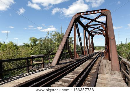 Railroad bridge with an old rusty arch. Blue sky, trees.