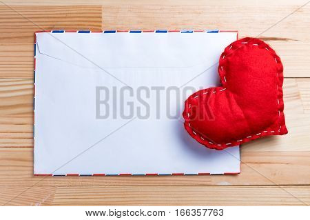 Red homemade heart on a love letter on Valentine's Day. Blank envelope. Natural wooden table. Copy space.