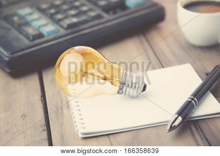 bulb on paper and calculator on table
