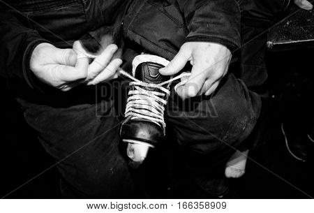 Close-up of a fathers' hands tying a boys' skate for his daughter in black and white