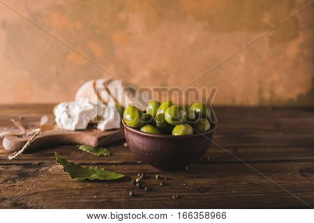 Green olives sliced ciabatta feta cheese on a wooden board. Spiced. Cheese Feta. Ciabatta. Olives on a orange abstract background
