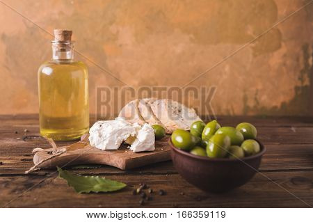 Green olives sliced ciabatta feta cheese on a wooden board. Olive oil in a glass bottle. Cheese Feta. Ciabatta. Olives on a orange abstract background