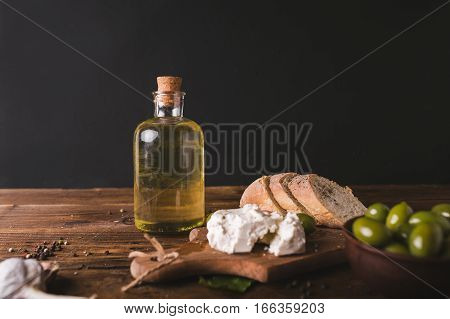 Green olives sliced ciabatta feta cheese on a wooden board. Olive oil in a glass bottle. Cheese Feta. Ciabatta. Olives on a black background
