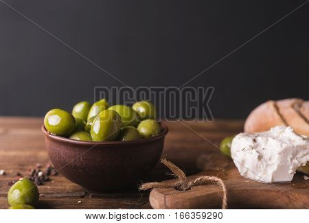 Green olives sliced ciabatta feta cheese on a wooden board. Cheese Feta. Ciabatta. Olives on a black background