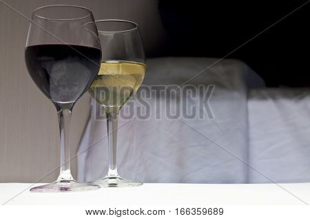 Two glasses of wine next to bed. Romantic evening.