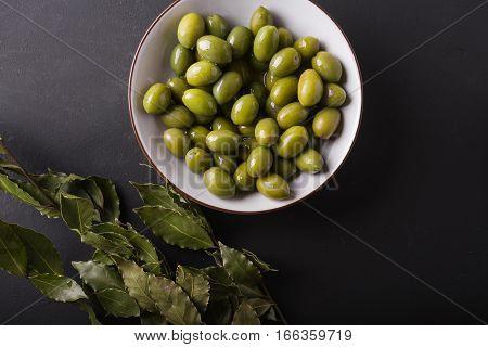 Green olives in a white bowl on a black background. Background of olives. Background with green olives. Olives. Bay leaf. Copyspace