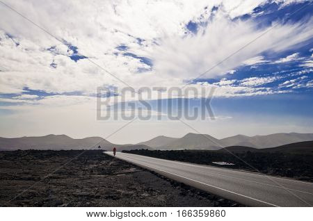 Volcanic landscape and cloudscape - road on Lanzarote. Timanfaya National Park
