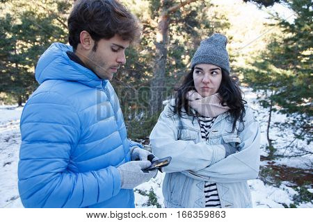 Handsome caucasian man talking on the phone while he passes from his girlfriend when they are on a date in the snow. It's a trip on a mountain holiday.