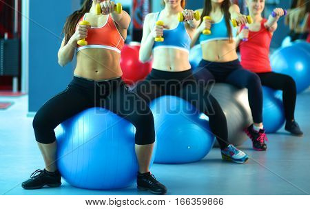 Group of people in a Pilates class at the gym .
