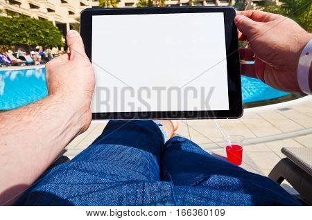 Man holding a tablet with blank screen sitting next to a hotel pool. Point of view photo.