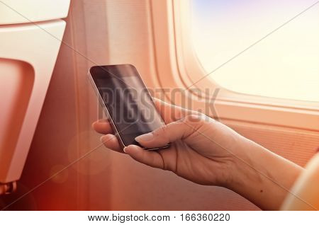 Using a mobile phone on a plane. Smartphone in woman's hand.