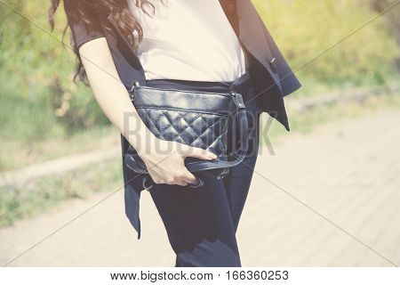 Young fashion woman hold handbag clutch in park